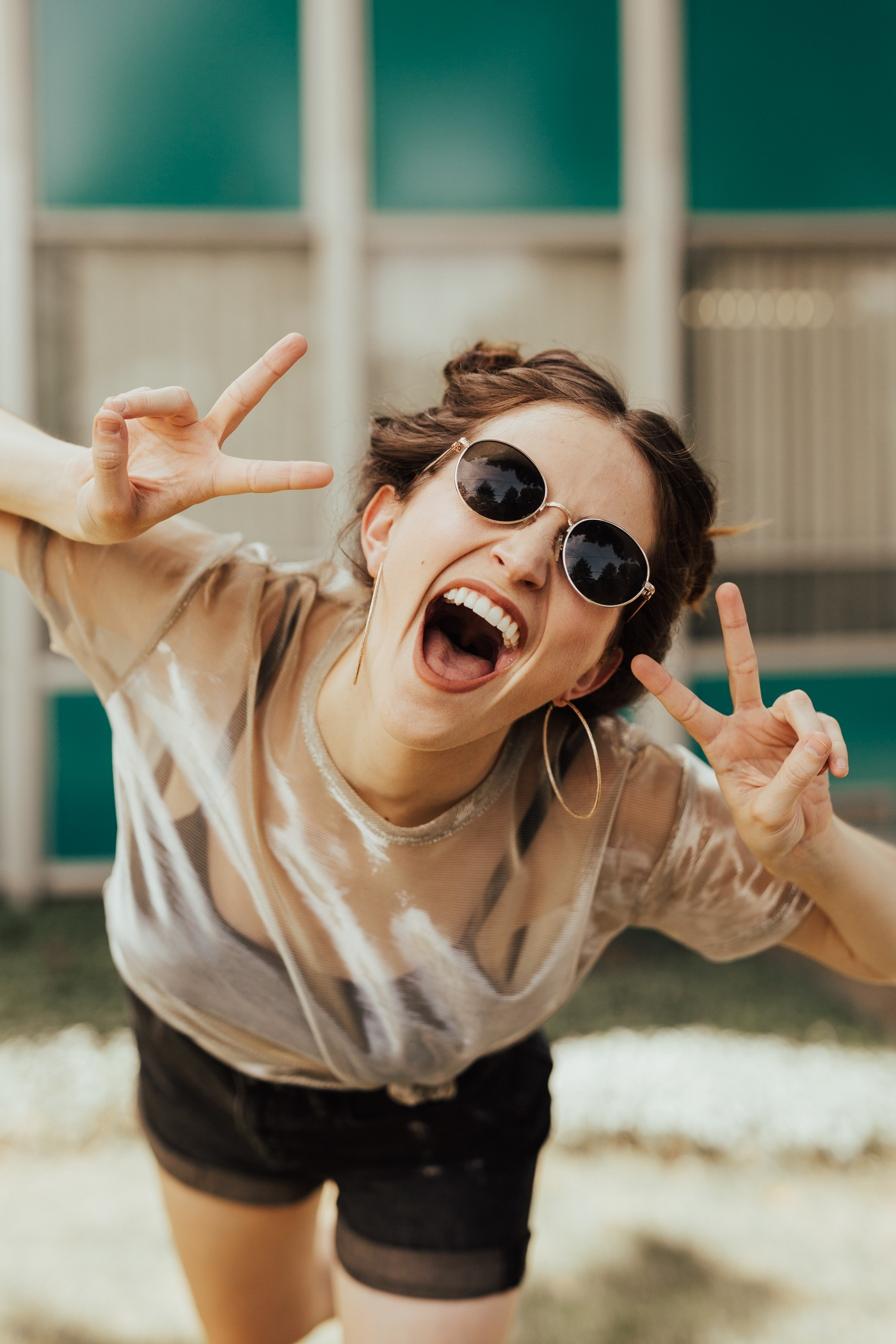 photo of young woman, mouth wide, sunglasses, two V-signs, happy