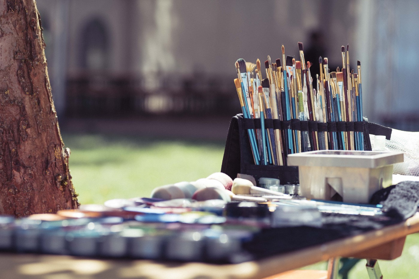 Close up of art-set consisting of dozens of brushes standing up and paint on a table outside in a park on a sunny day.