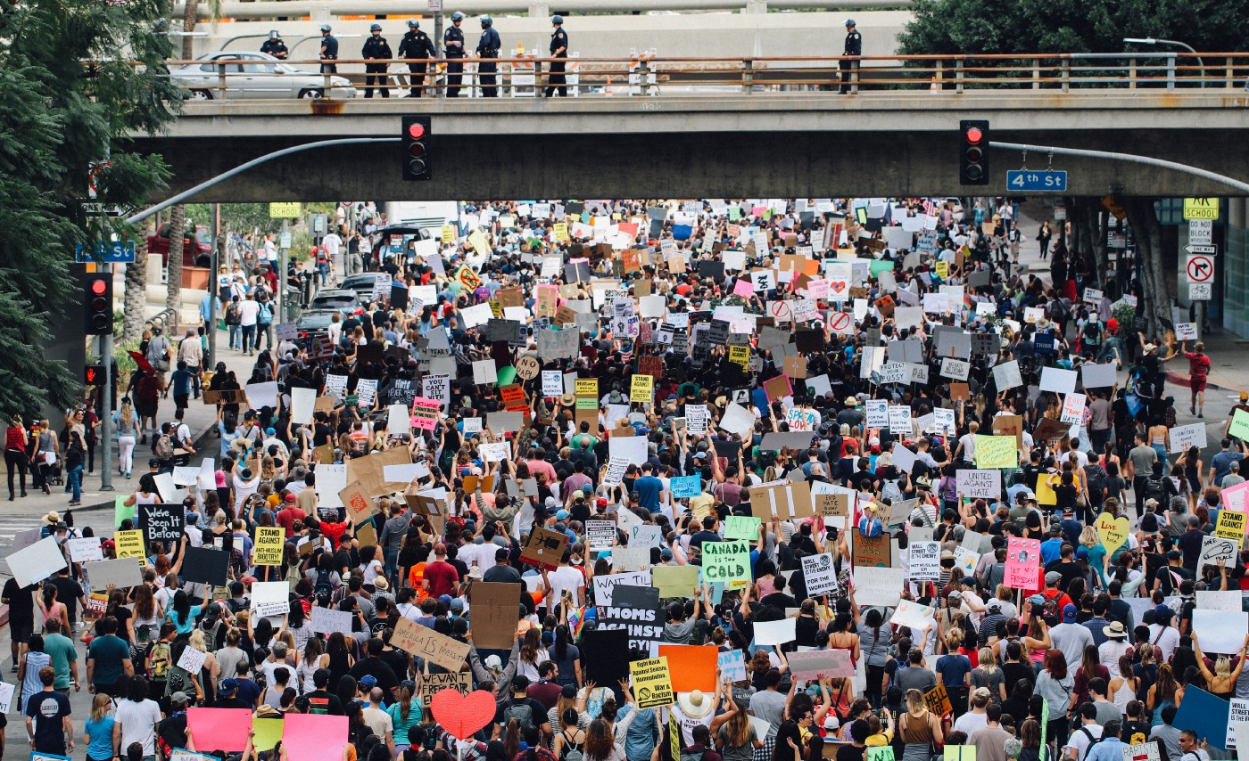 A panoramic photo of a big crowd protesting underneath a bridge, with various cardboard cutouts.