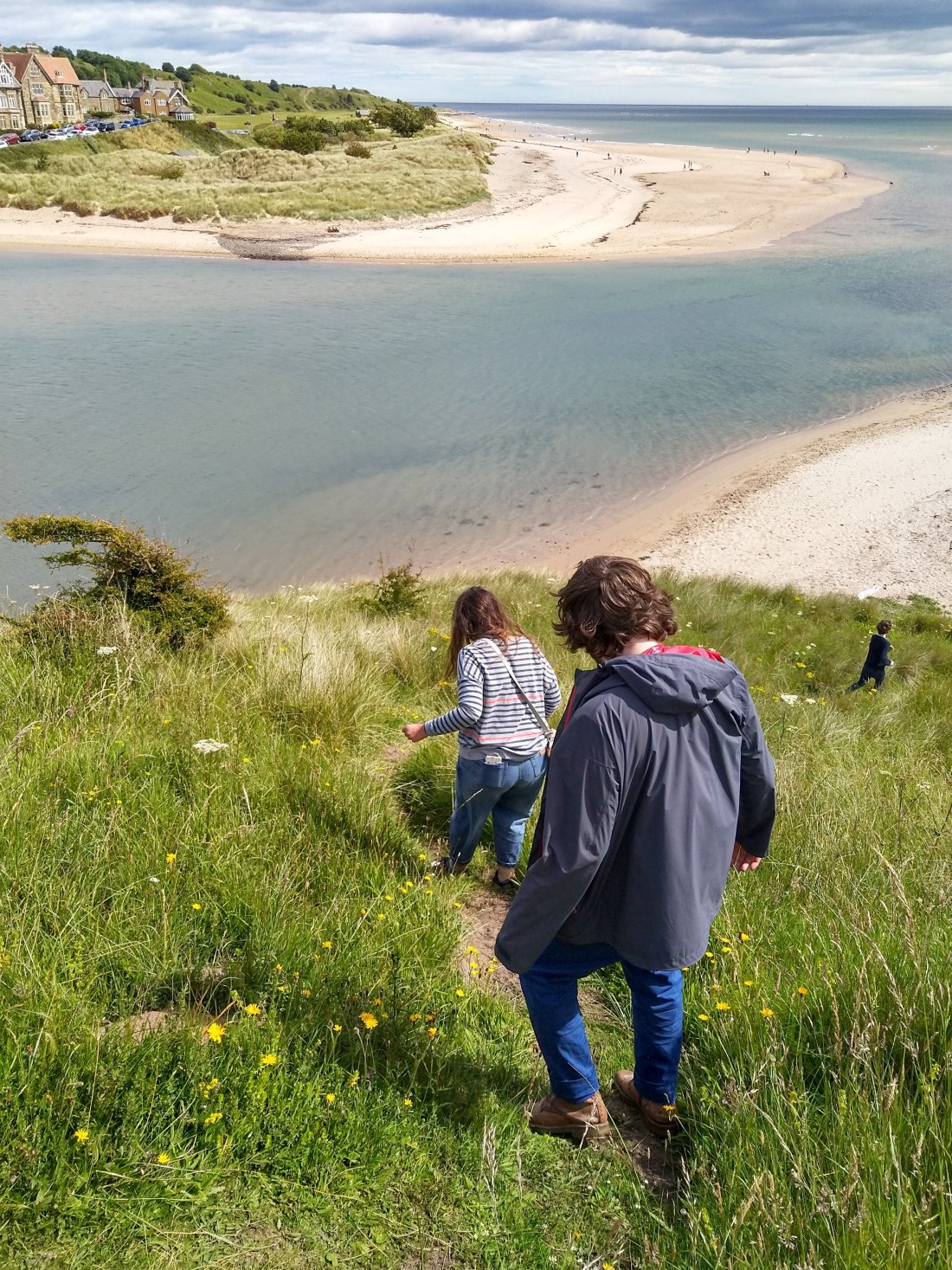 Three people walking down a steep path to a beach