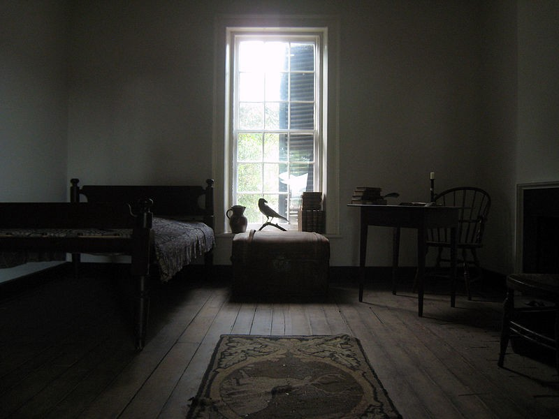 A small, dark, 19th century-style  room with a raven statue in front of a sunlit window.