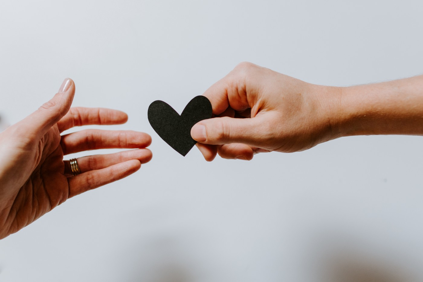 One person hands another a black paper heart.