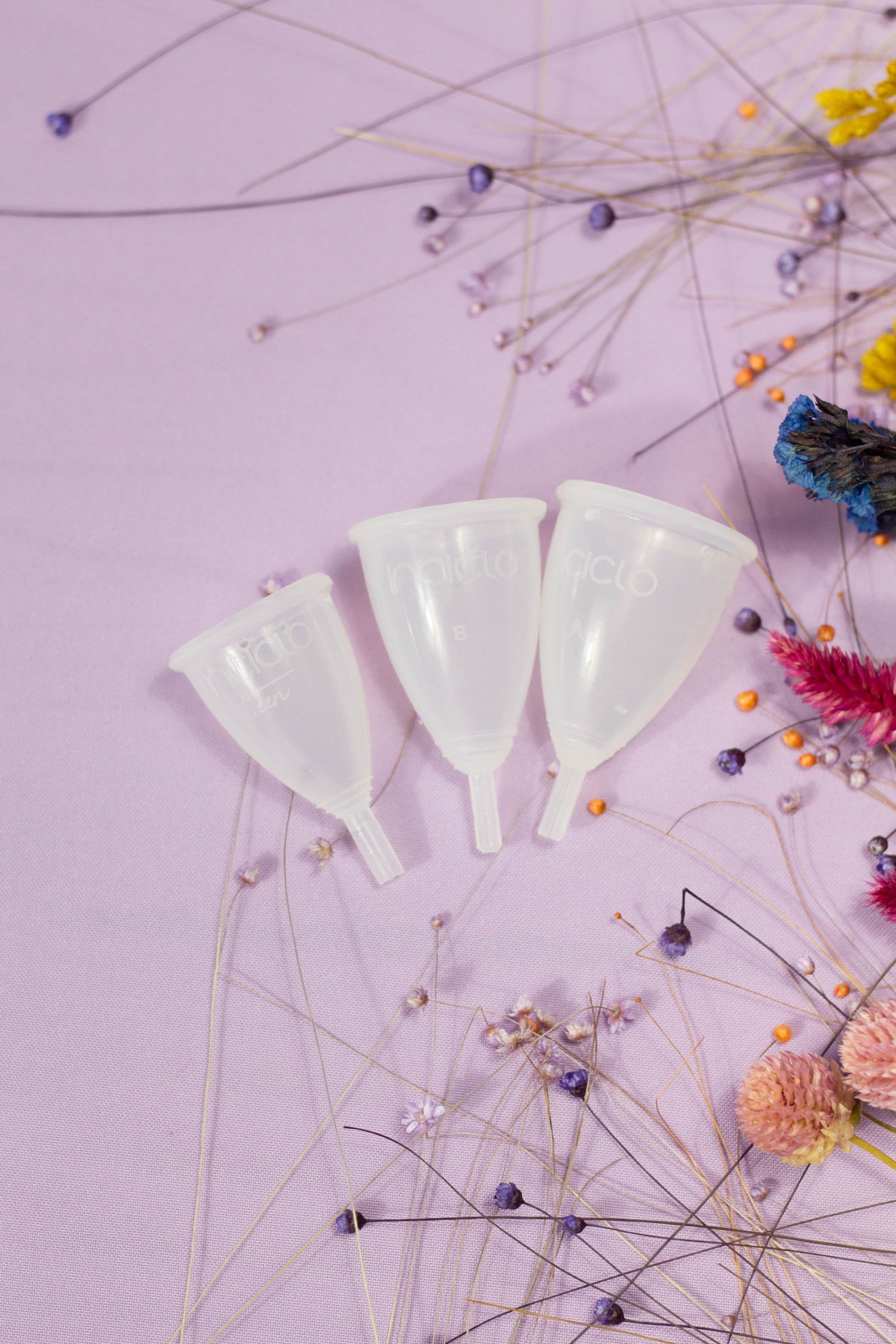 three white menstrual cups of three different sizes on a purple surface