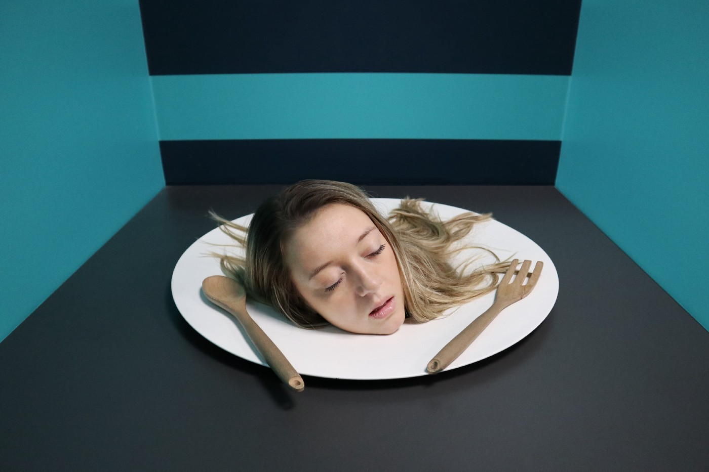 image: woman's head on a white dinner plate between a spoon (left) and fork (right); the background is black and teal.