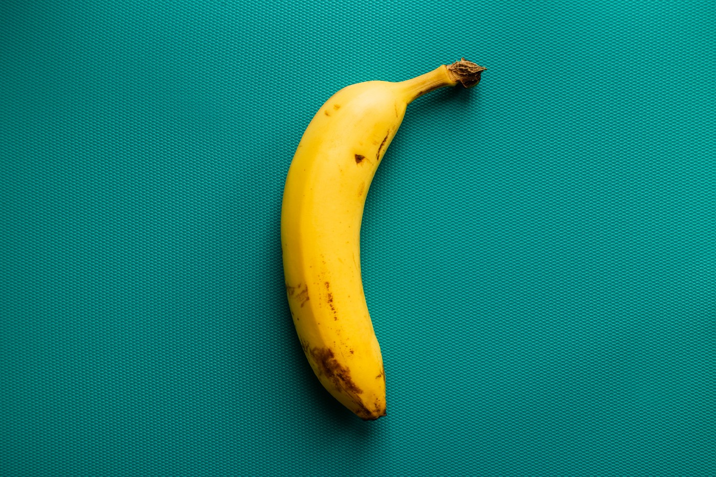A photo of a banana against a teal background.
