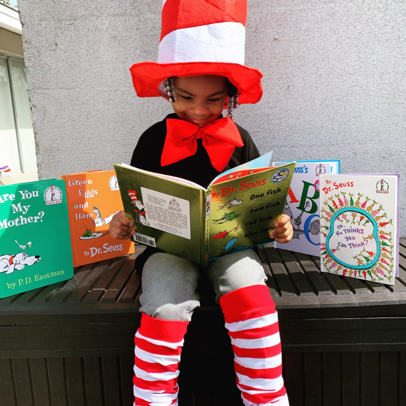 Child reading Dr. Suess books with several Seuss books standing up around her.