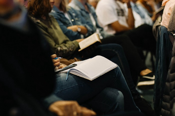 Close up of a person's lap, with a notebook resting on it and a pen in hand. They are sitting with other people at a conference