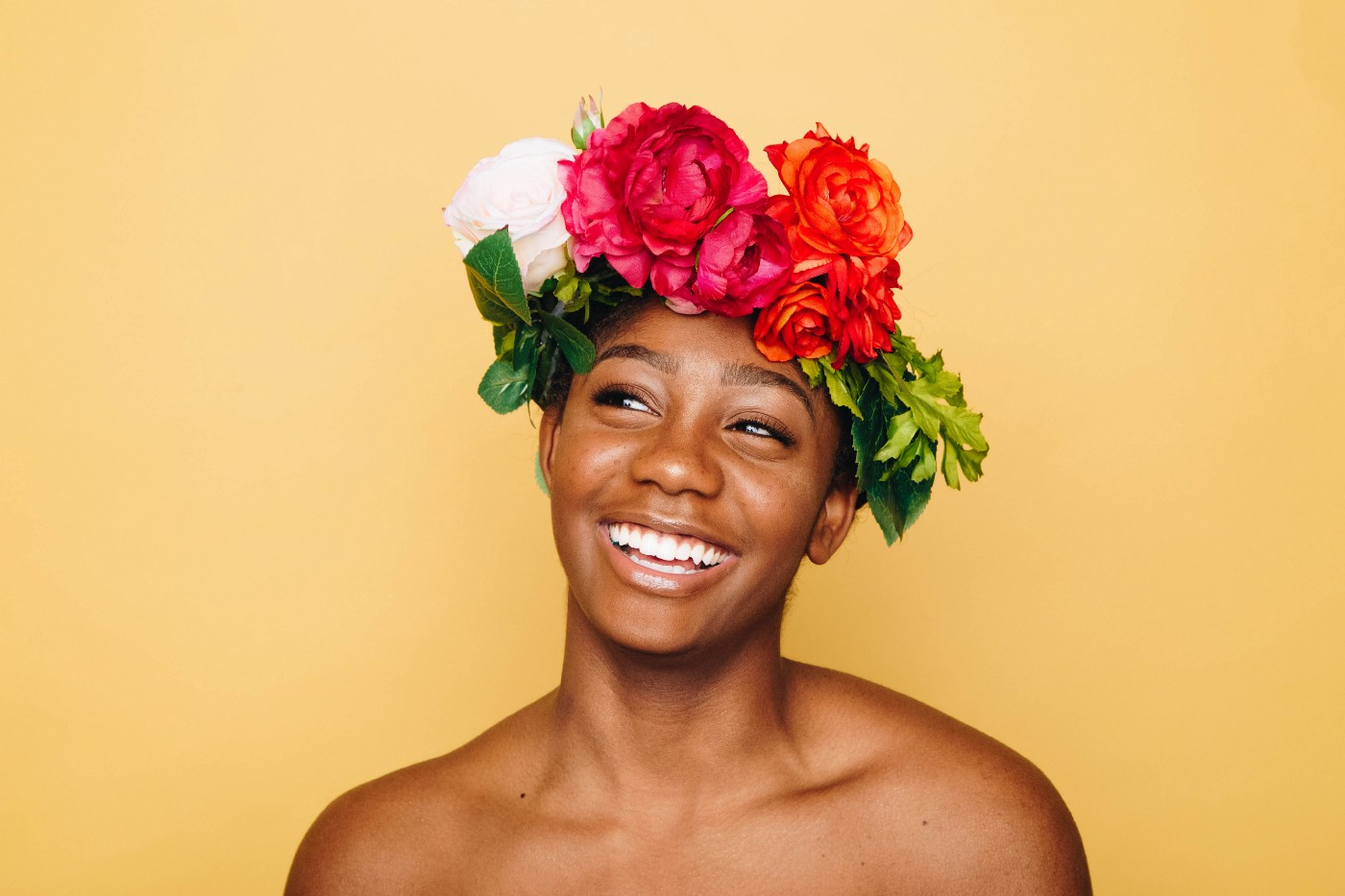A shoulders-up view of a person with a flower crown, smiling, in front of a yellow background.
