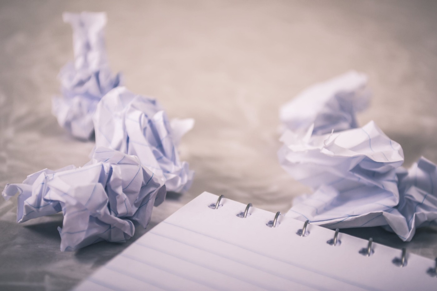 Two crumpled up pieces of paper sit next to a notebook