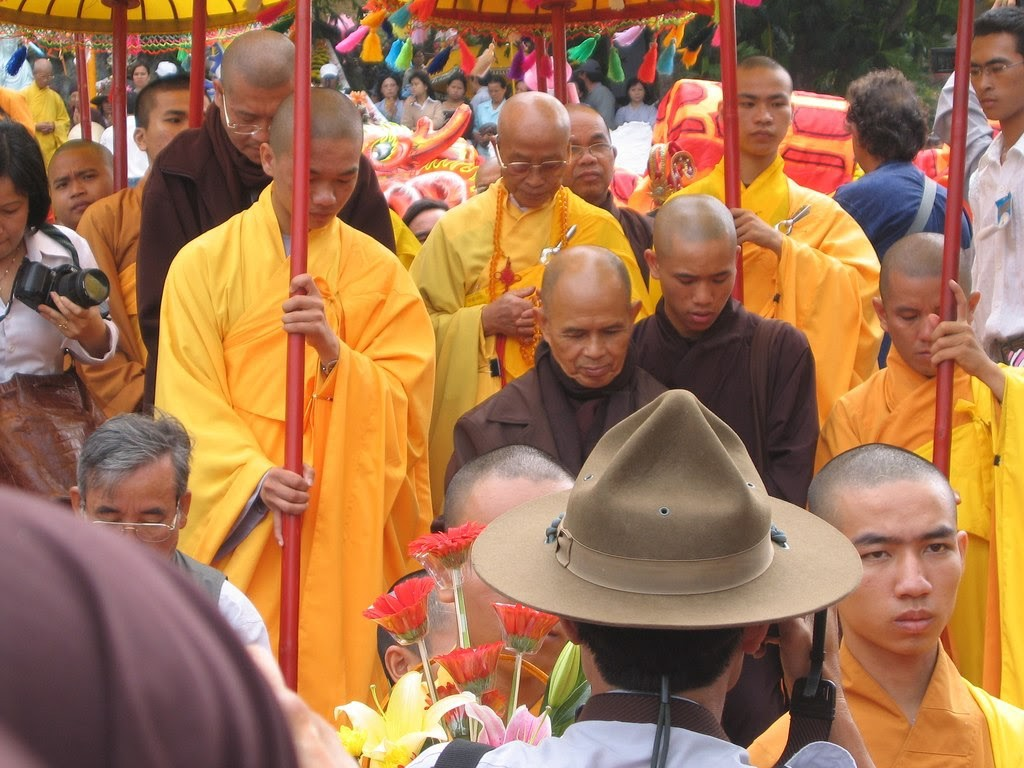 Thich Nhat Hanh in brown Buddhist robes surrounded by other Buddhist monks in yellow robes.