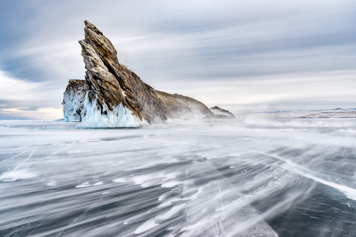 A rock covered in snow jutting out of a frozen lake