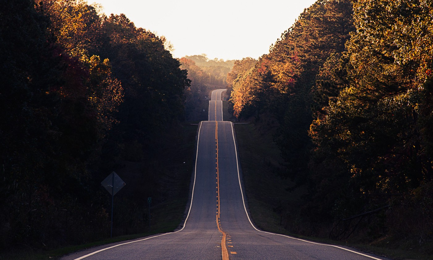 Two lane black top road with three hills. Surrounded by dense trees.