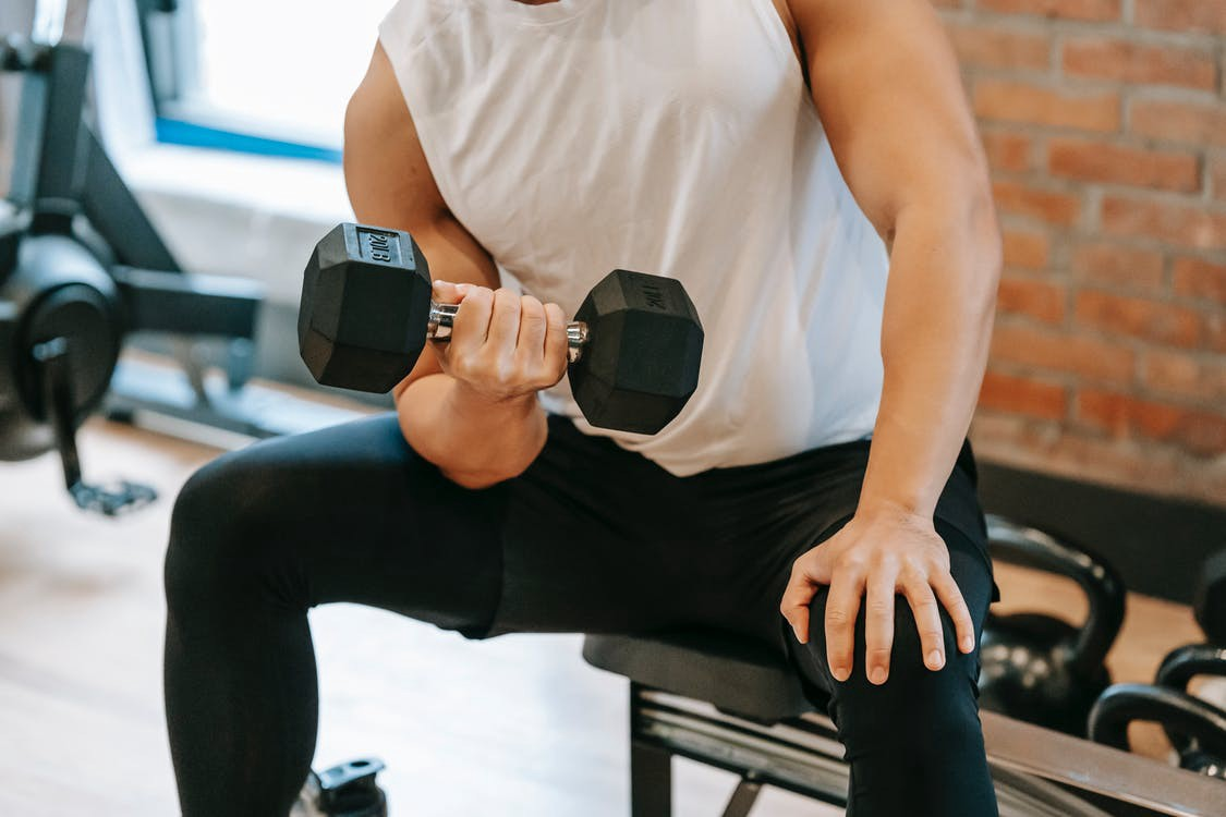 Man sitting down and curling dumbbell