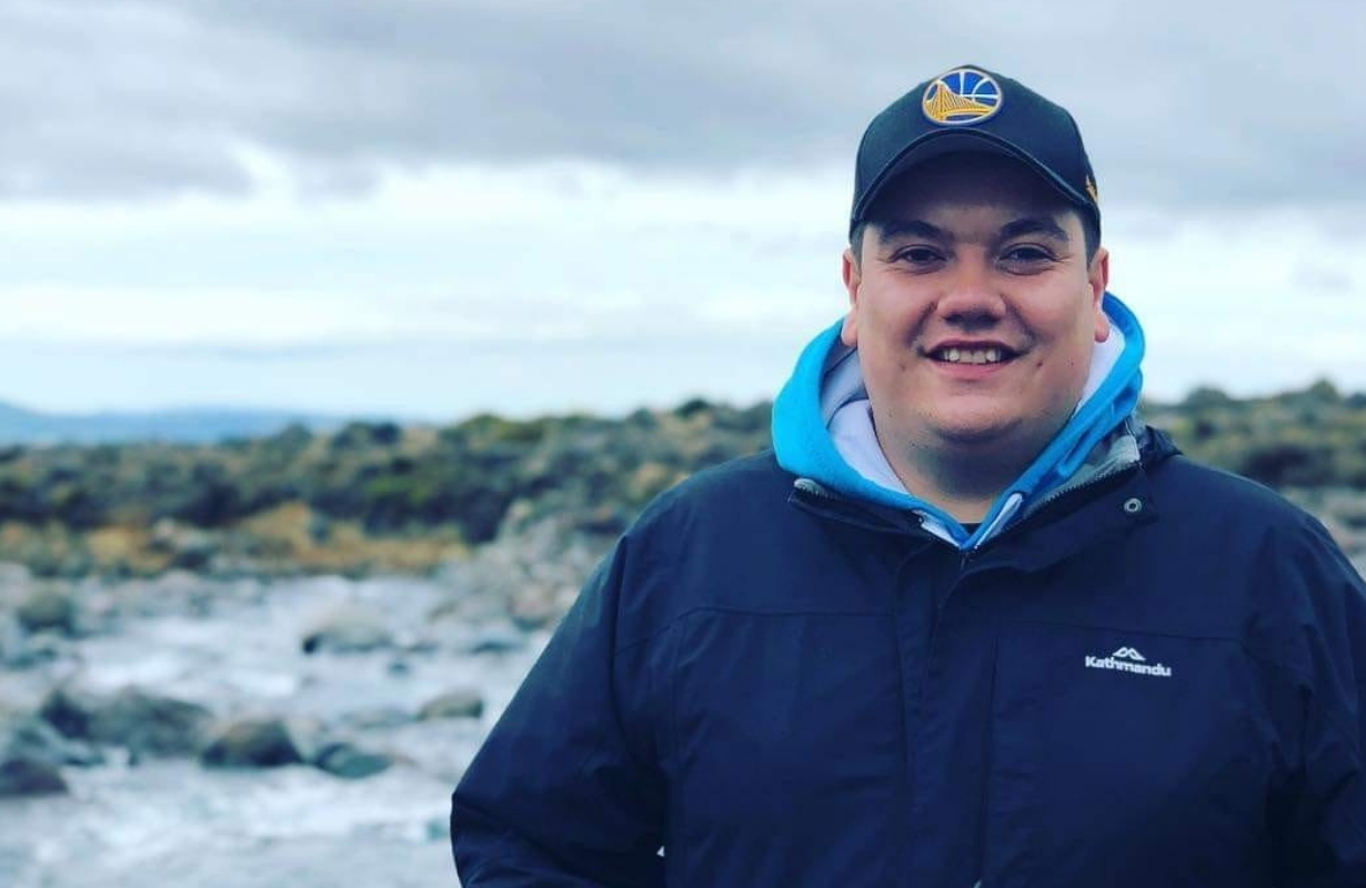 Elijah at a rocky beach, smiling to camera in jacket and cap
