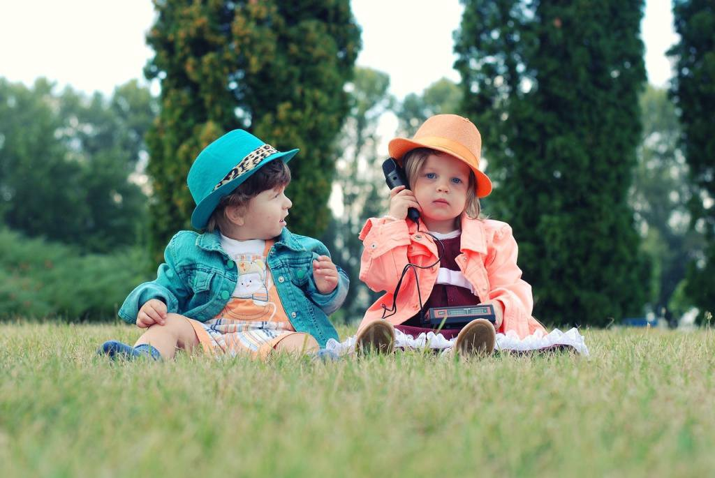 Two toddlers sitting on the grass: are they born leaders?