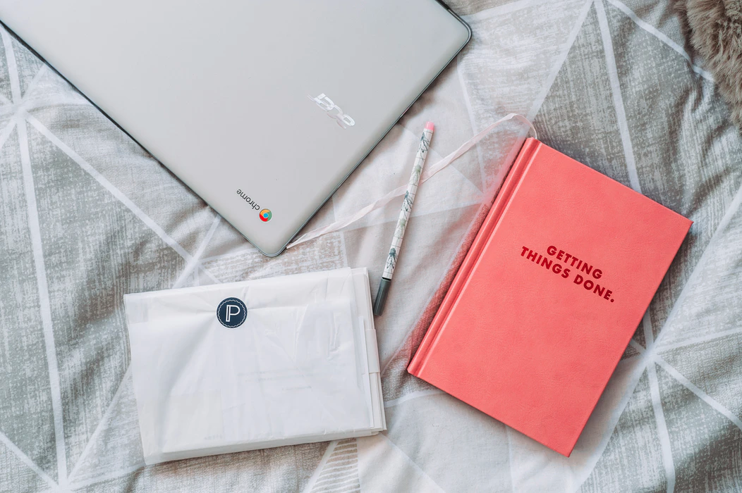 """Two notebooks and a laptop on a bed. One of the notebooks says on the cover, """"Getting things done"""""""