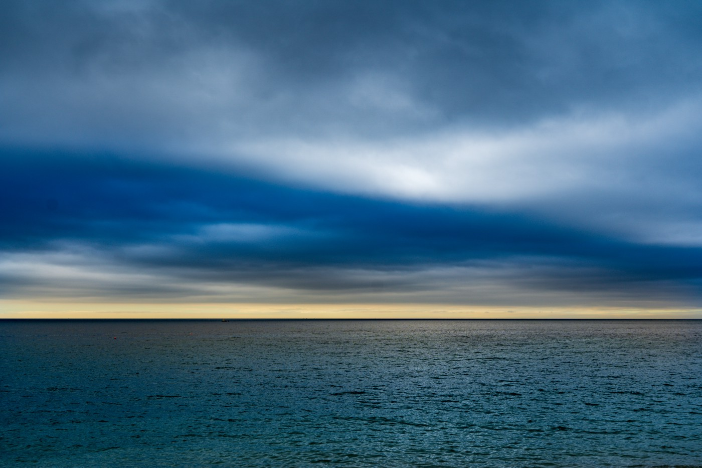 Photo of the horizon with dark clouds and sun peaking out from behind.