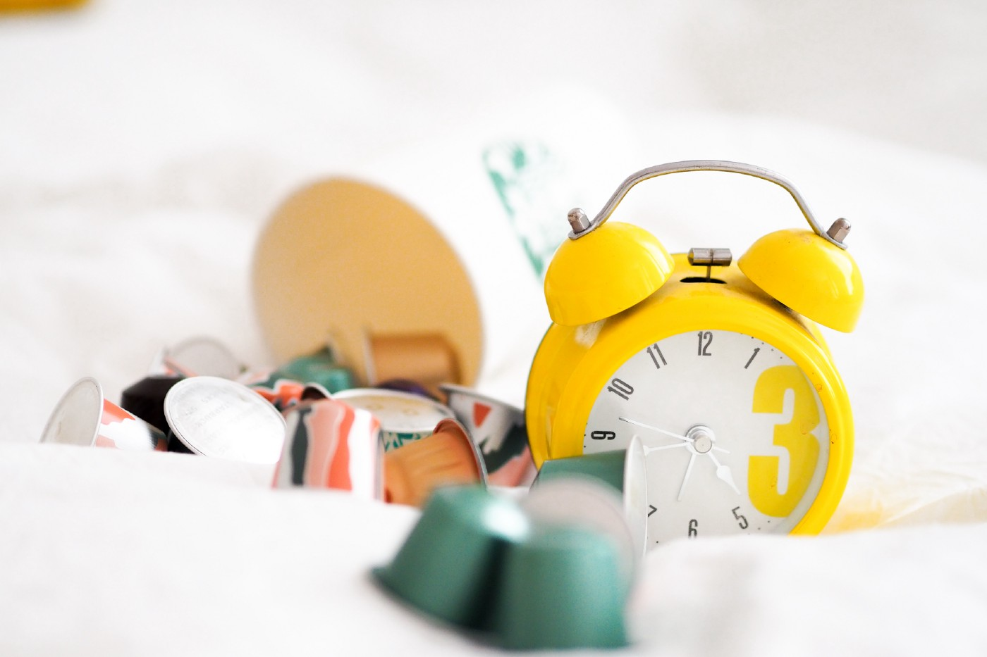 Bright yellow clock amid out of focus items scattered around it.