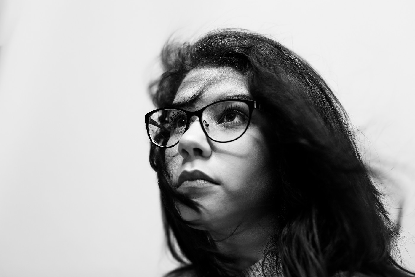 A picture of a girl with glasses looking off into the distance with a confident and determined expression on her face.