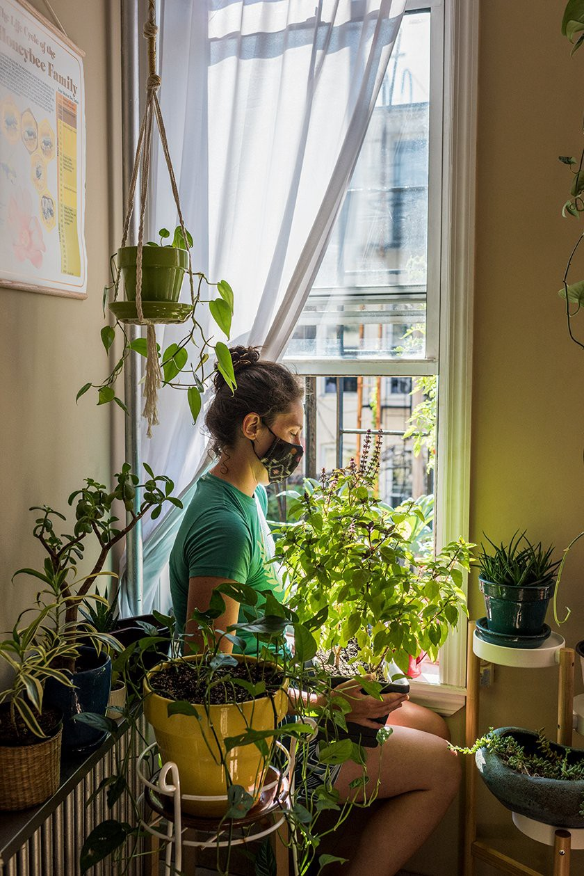 Urban growing is about utilizing the space, whether an expansive surface on a roof or the windowsill. Here we see beekeeper Geraldine Simonis moving her Thai basil plant onto her New York fire escape garden. (Photo: Valery Rizzo, Urban Farmers)