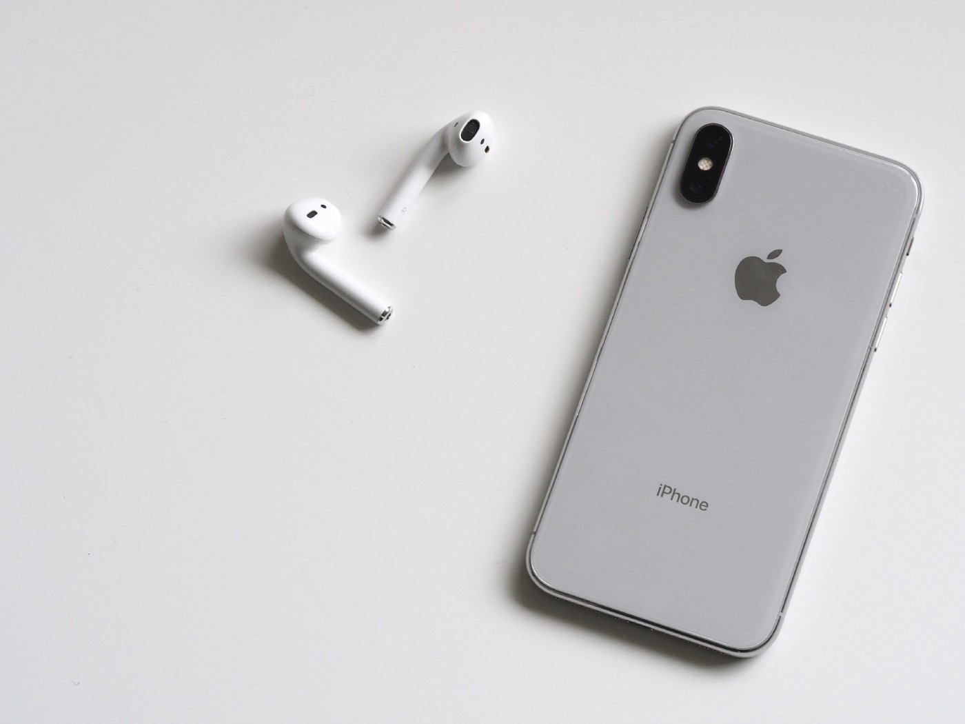 A picture of a phone and airpods disconnected on a table.
