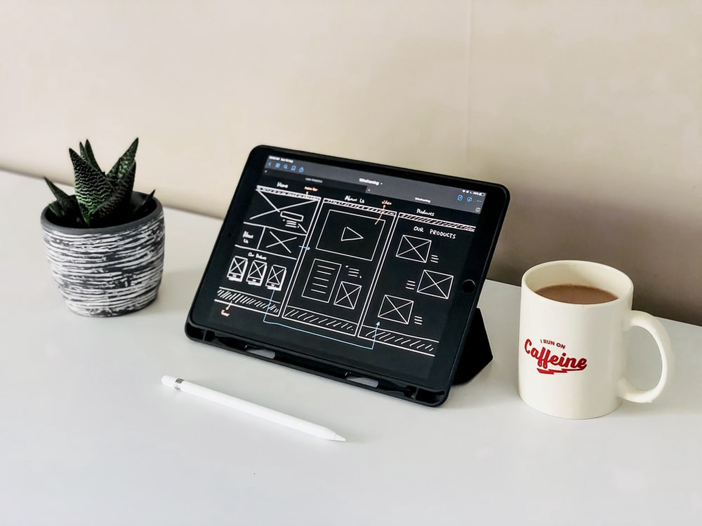 black ipad beside white ceramic mug on white table. This ipad has facilities for jobs for web designer, a graphic designer for website should need this.