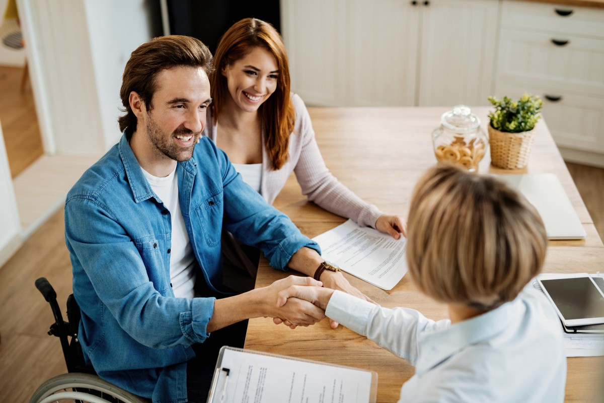 A. woman with brown hair, sits at a table, behind a man in a wheelchair wearing a light blue shirt with long sleeves. He shakes the hand of another person with short blonde hair—she holds a clipboard. They are all smiling.