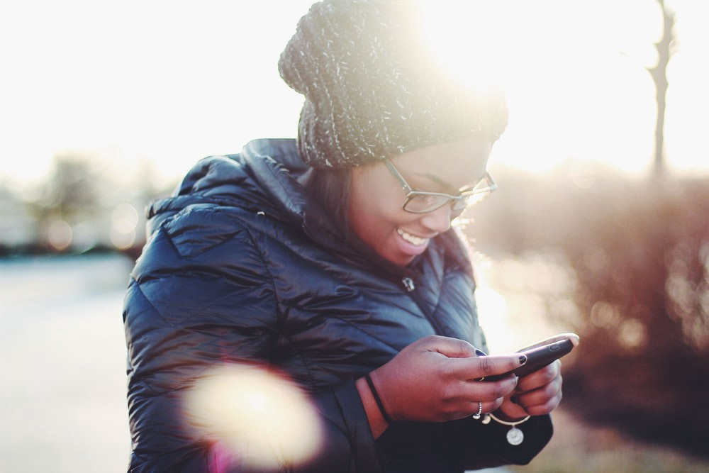 Girl smiling at phone in the sunlight