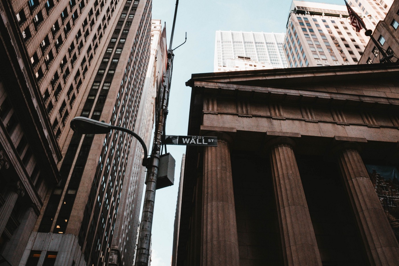 """A stone bank with a streetlight that reads """"Wall Street"""""""