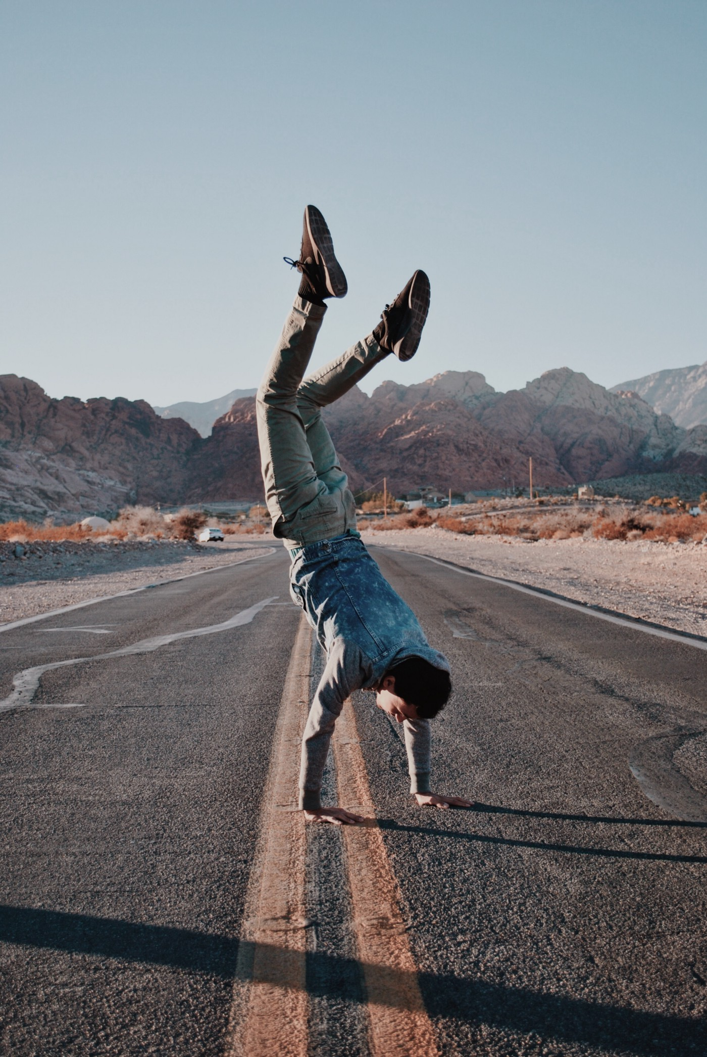 photo of a young man in the middle of a desert road doing a hand-stand