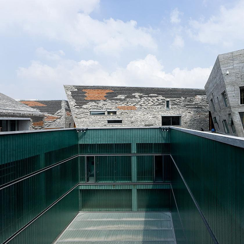 Just to the north of Yinzhou Park in the city of Ningbo, the Ningbo Historic Museum occupies space in a massive plaza landscaped with fountains and newly planted trees. Inspired by a mountain landscape rather than the urban one it serves, the three-story building is an enormous hulking form with impressive outward-sloping walls. (Photo: Iwan Baan for Amateur Architecture Studio, Beauty and the East)