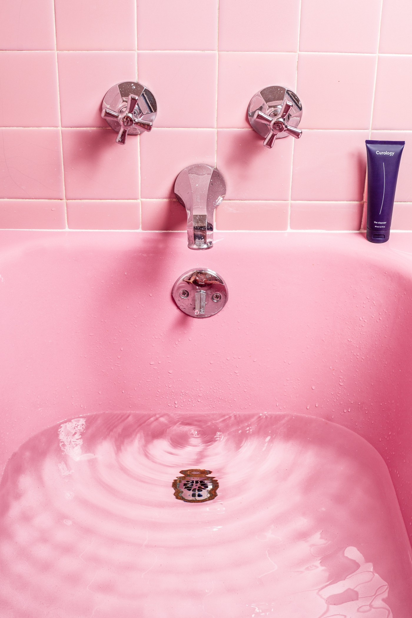 "Pink bath tub filled with rippling clear water. Pink bathroom tile and silver faucet. Dark purple tube of Curology ""the Cleanser"" body care product on the right side of the tub faucet."