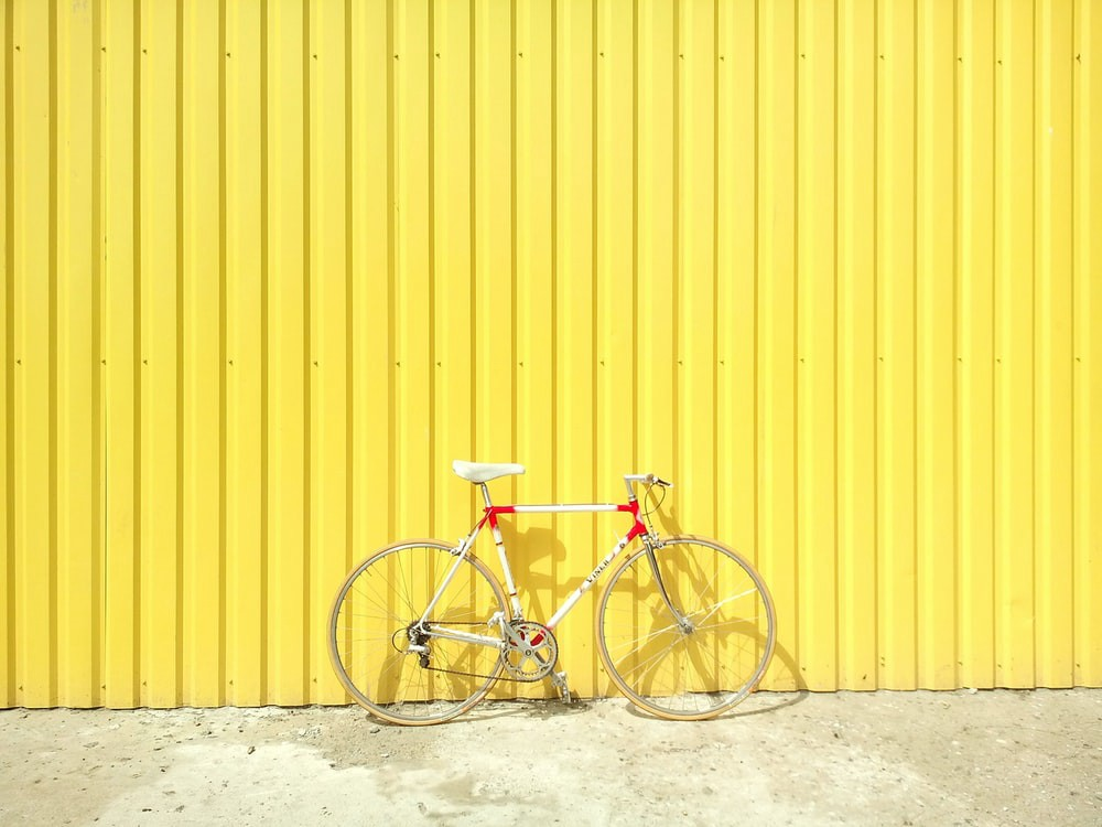 Bicycle in front of yellow wall