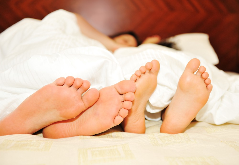 Couple lying in bed under sheets with the focus on feet