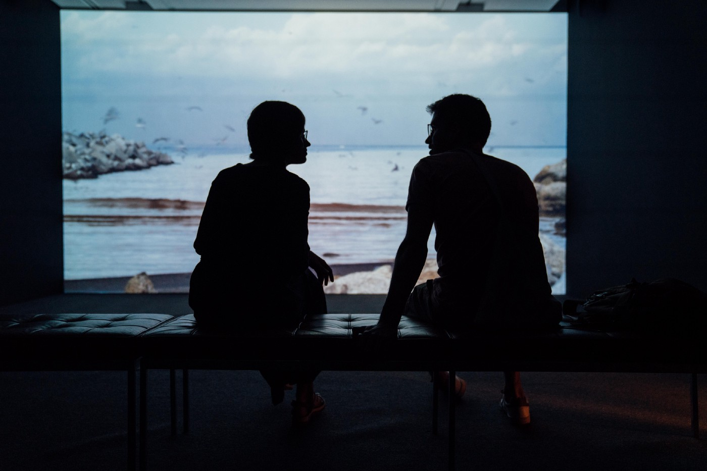 Two people sit indoors on a bench in front of a large window or screen. The people are in silhouette.