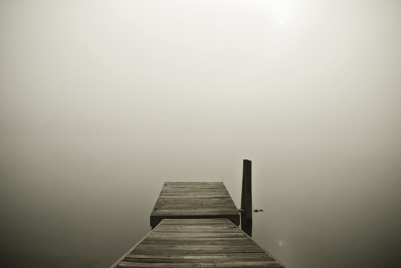 A crude wooden pier disappearing into mist