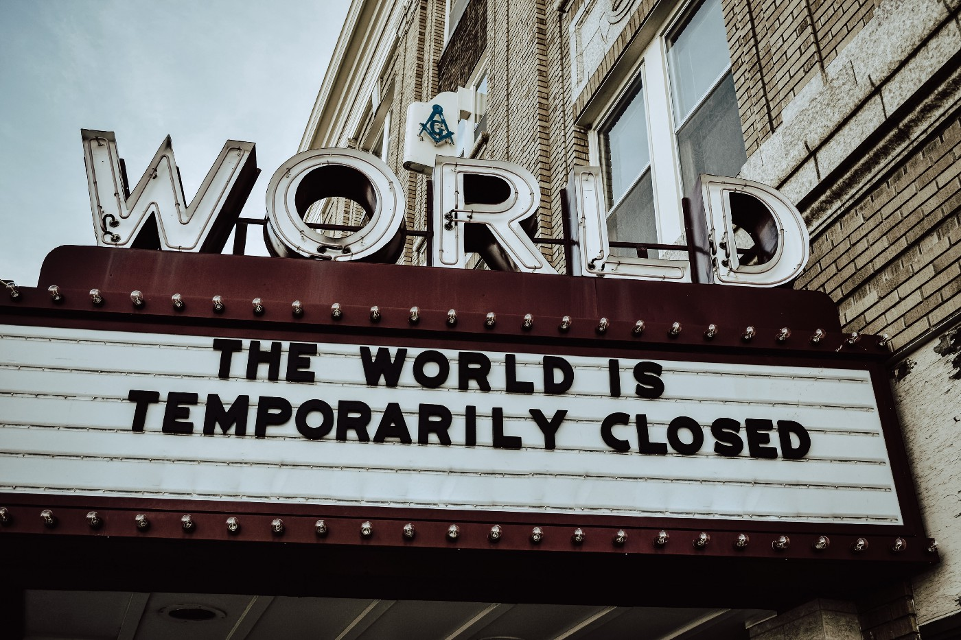 """Photo of a cinema marquee featuring the quote, """"The world is temporarily closed."""""""