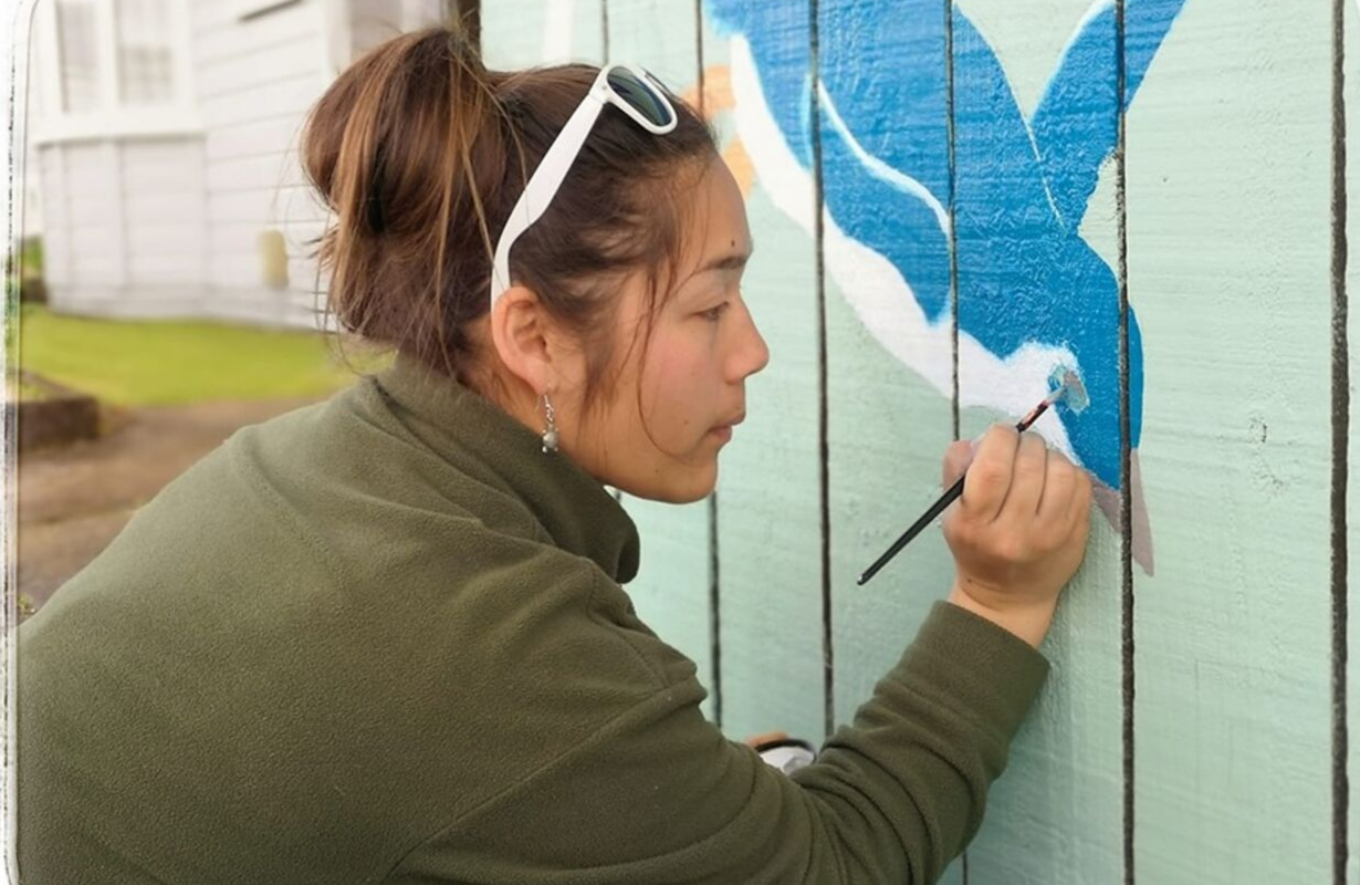 Elvisa is painting a swimming penguin onto a fence