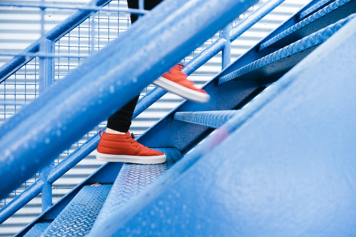 A person with red shoes walking up blue steps; side angle