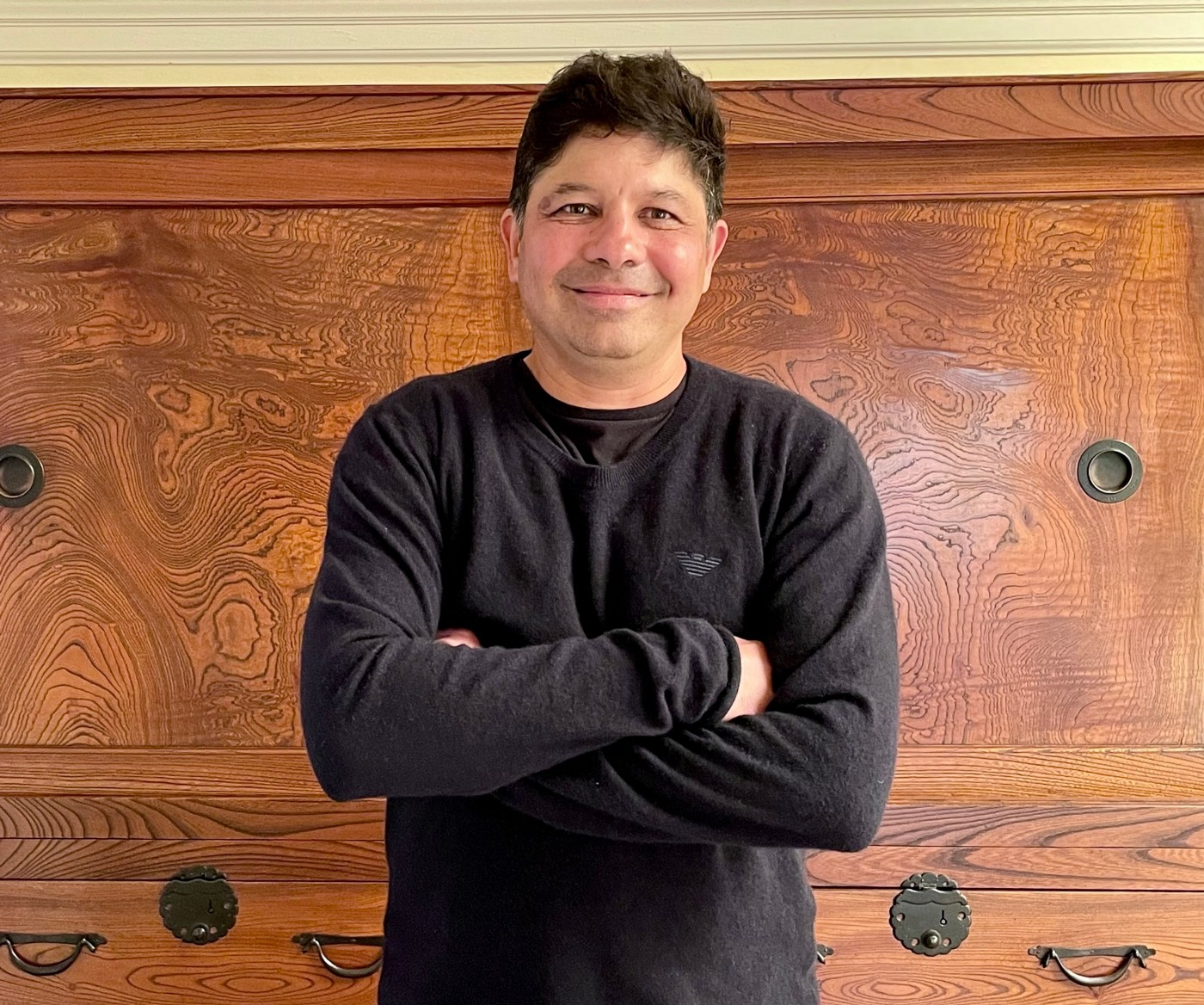Man in sweater stands with arms folded, smiling at the camera.