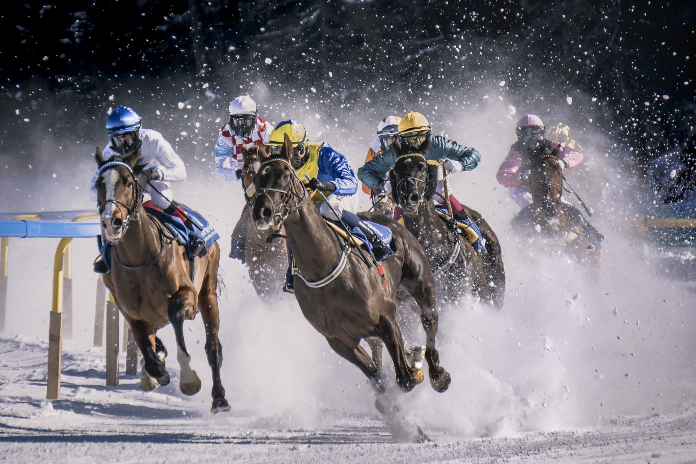 Horses racing on a track lightly covered in snow