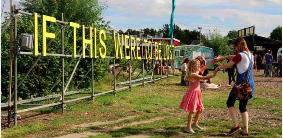 Children and adults dancing by sign saying 'If this were to be lost' by community garden in Peterborough