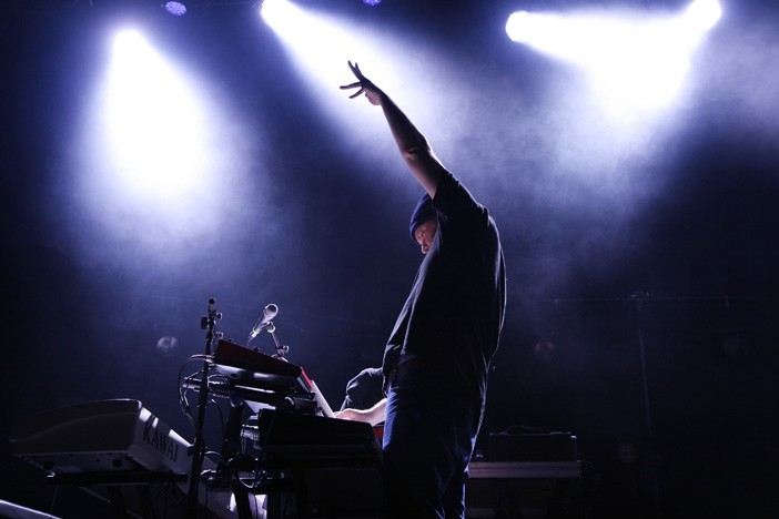 John Grant pulling a pose on stage with his arm in the air
