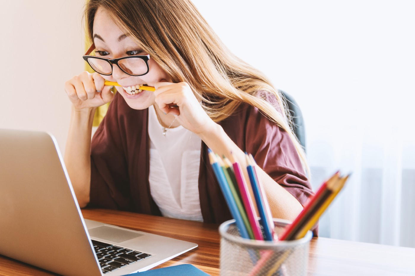 woman sitting at desk in front of laptop biting pencil in clear frustration