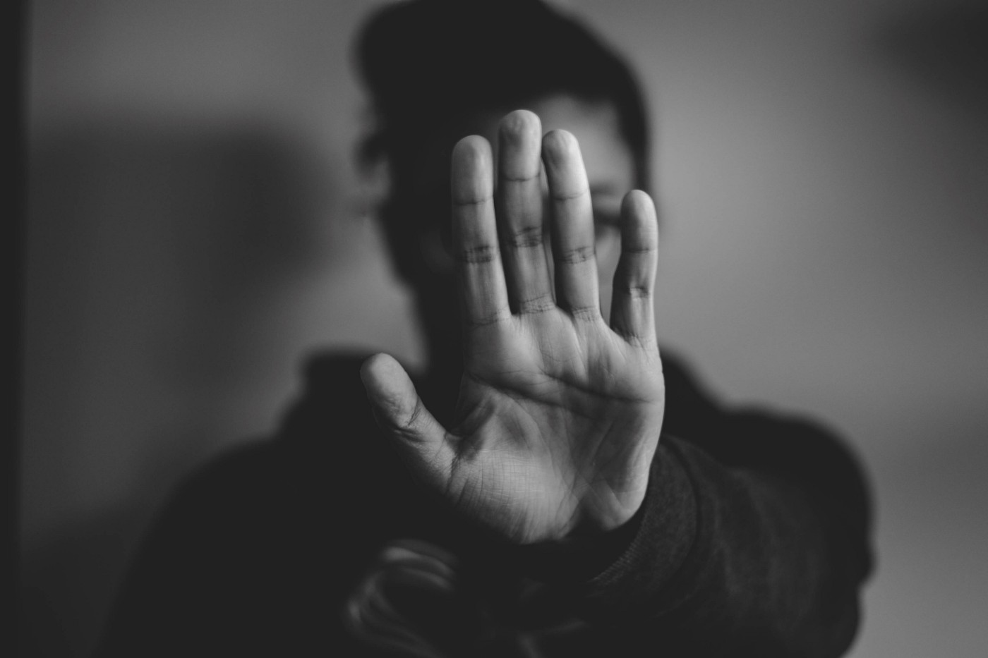 A person holding up their left hand as gesture to stop.
