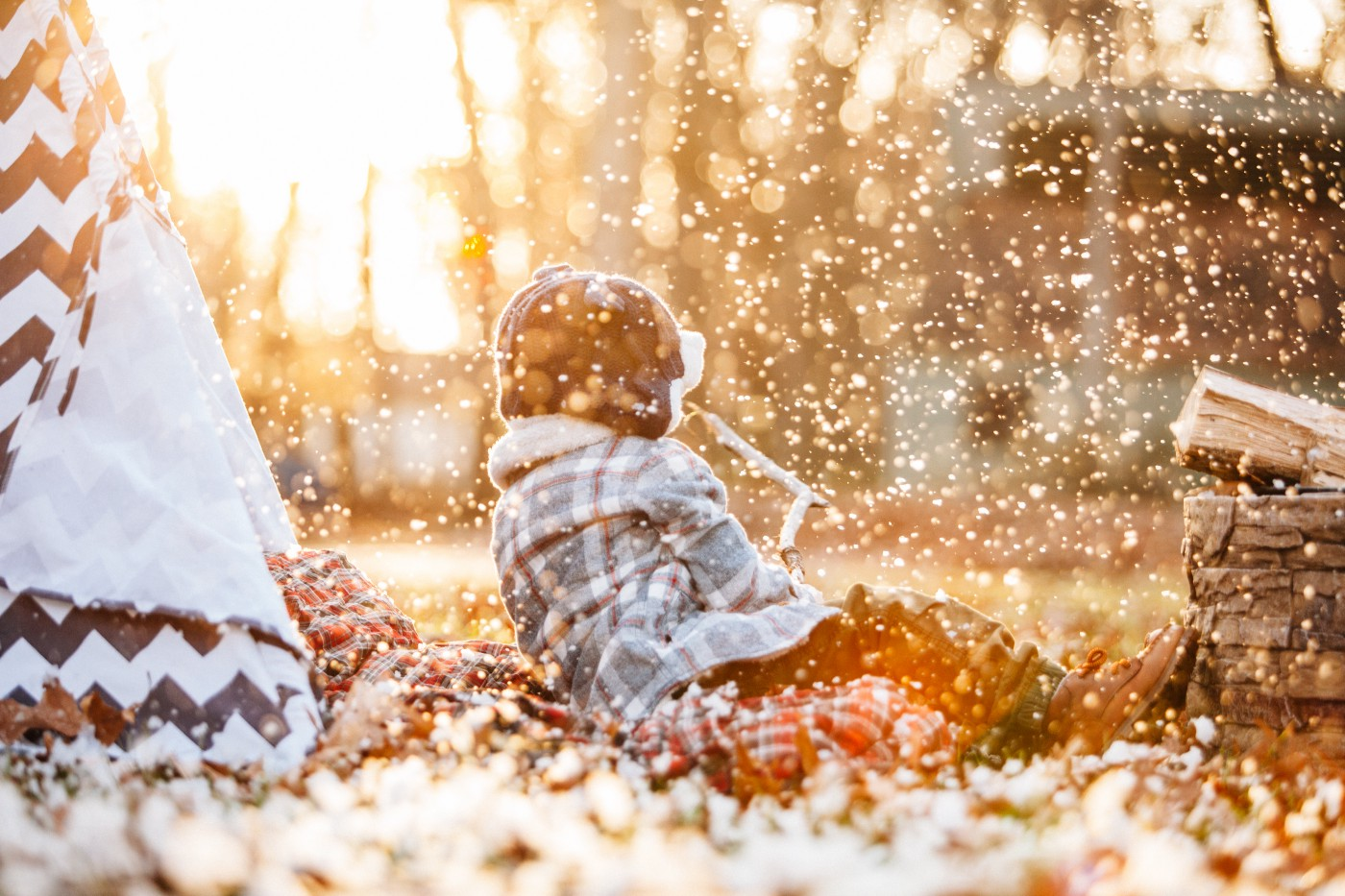 A child outside near a play tent, in golden light with glittering snow all around
