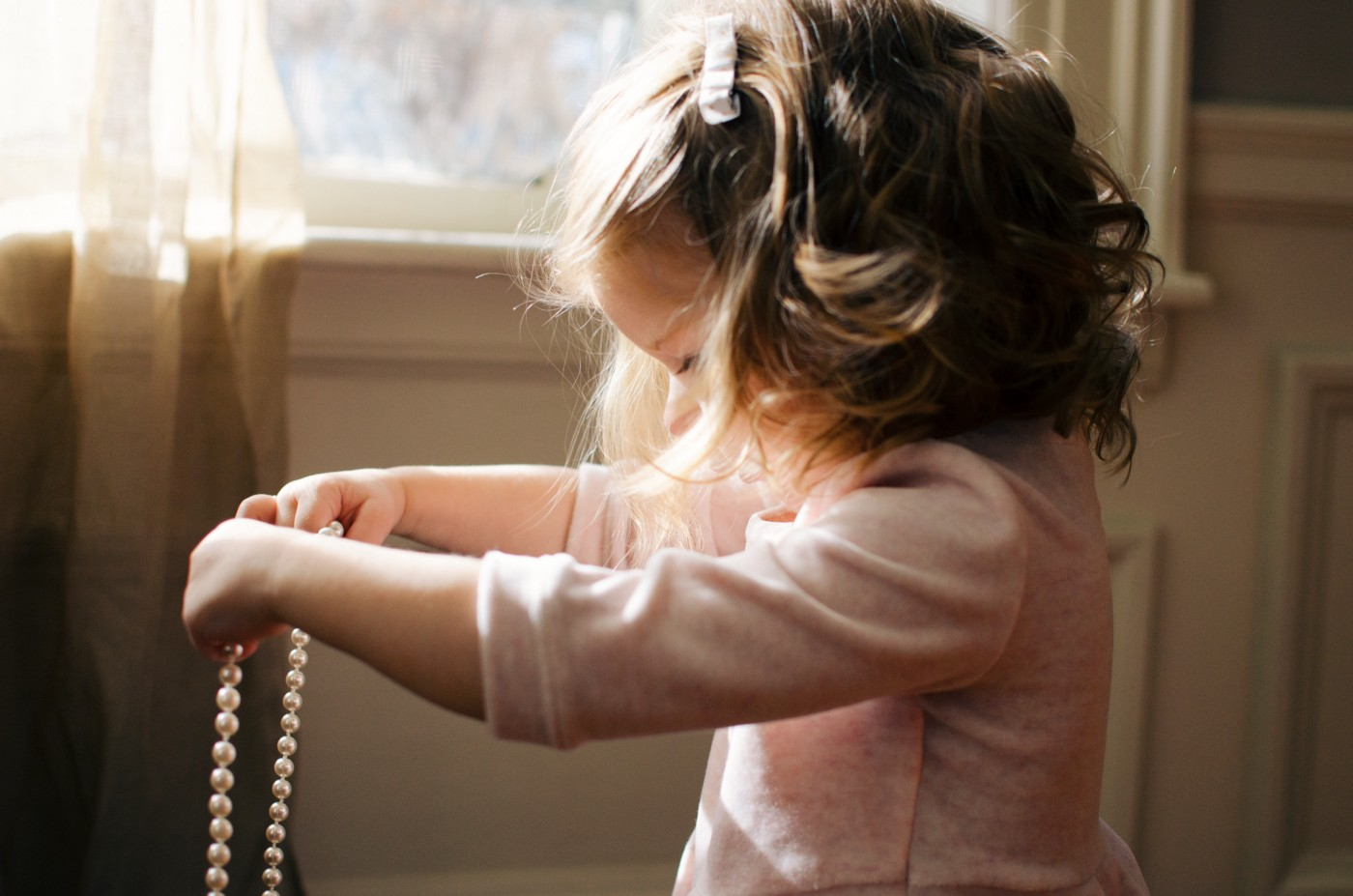 A side-view of a little girl, barely the height of the windowsill, wearing a pink dress holding out a string of pearls as if determining to put them around her neck. Her hair short and wavy but maturely coiffed like a woman's but with a barrette. A representative photo of a girl growing up too fast against more idealistic fashion.