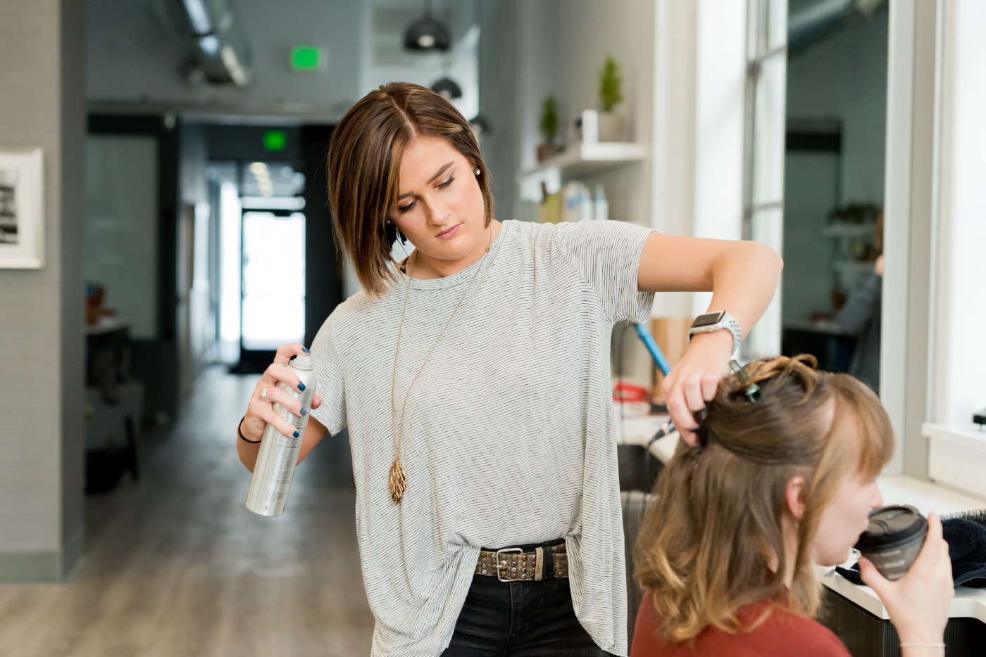 A young hairdresser wearing a white top was blowing a client's hair while she drinks coffee.