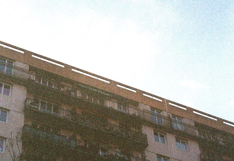 Film photo of building's top floors and blue sky