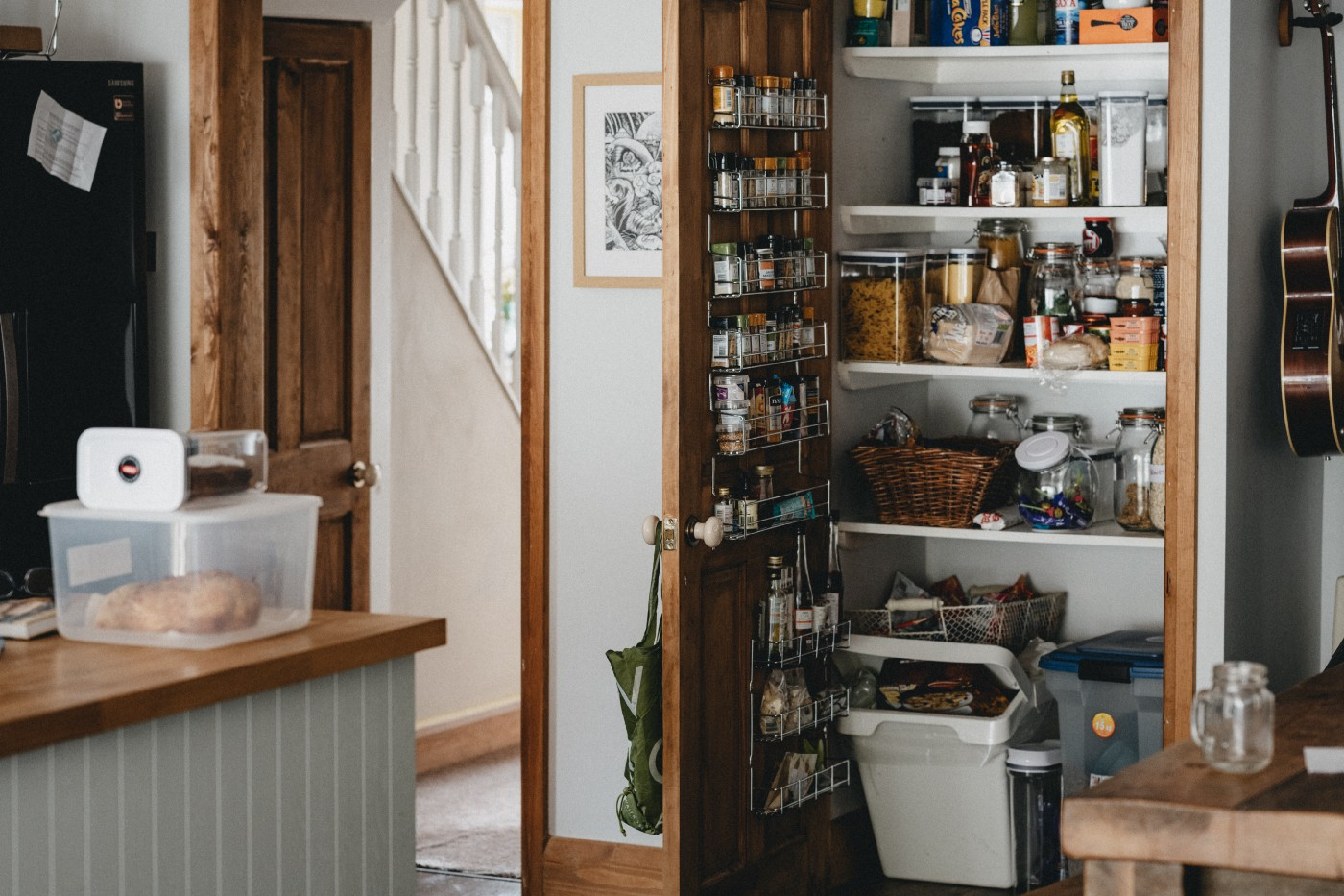 A neat farmhouse kitchen. The well-stocked pantry door is open.